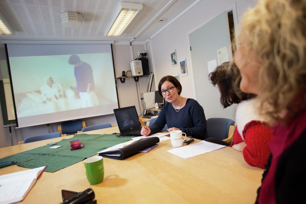 Kvinner rundt et bord med visning av helsearbeid på projektor. Foto.