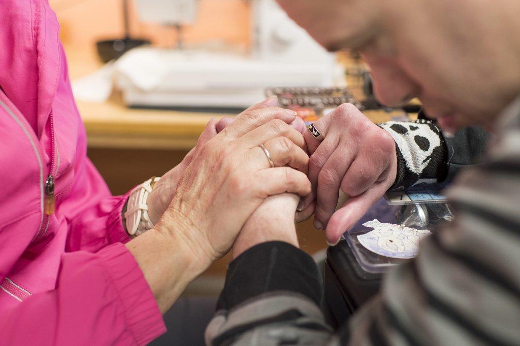Person holder hender til person med utviklingshemning. Foto.