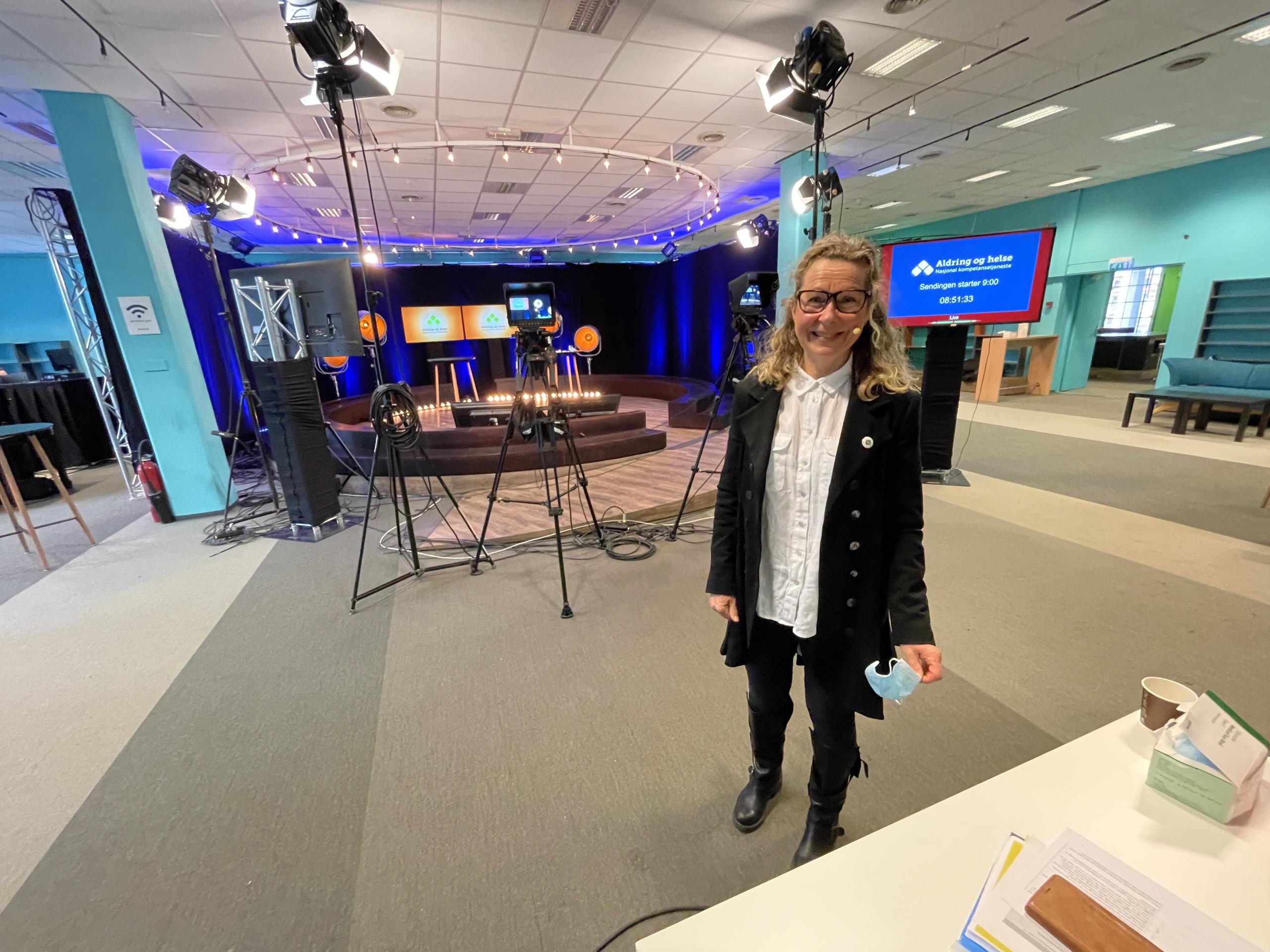 Kvinne smiler i studio. Foto.