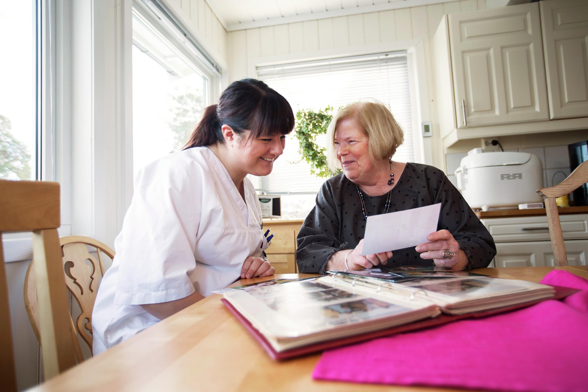 Kvinnelig helsearbeider ser på bilder sammen med hjemmeboende pasient. Foto.