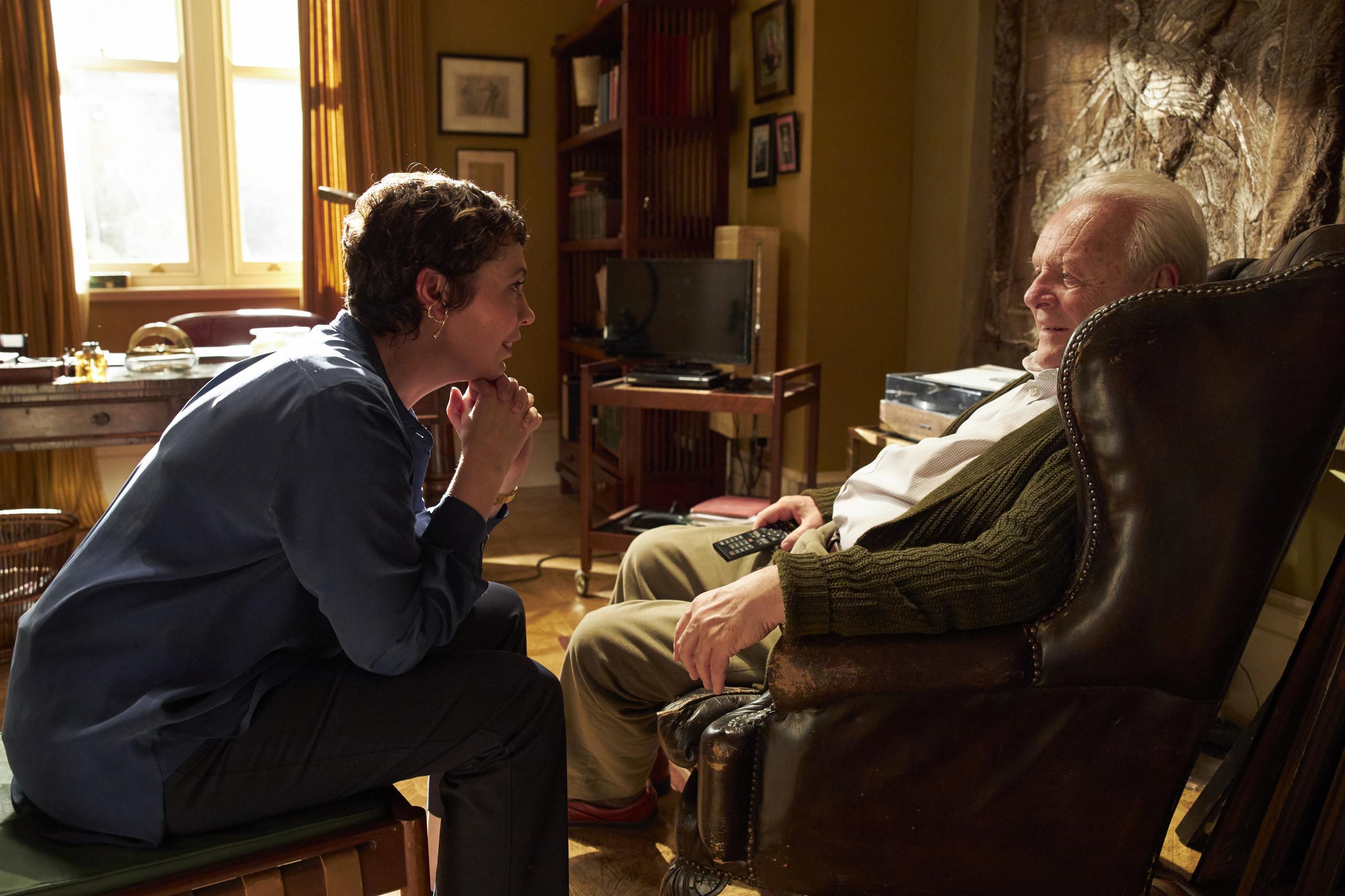 Mann sitter tilbakelent i stol og snakker med kvinne. Foto.