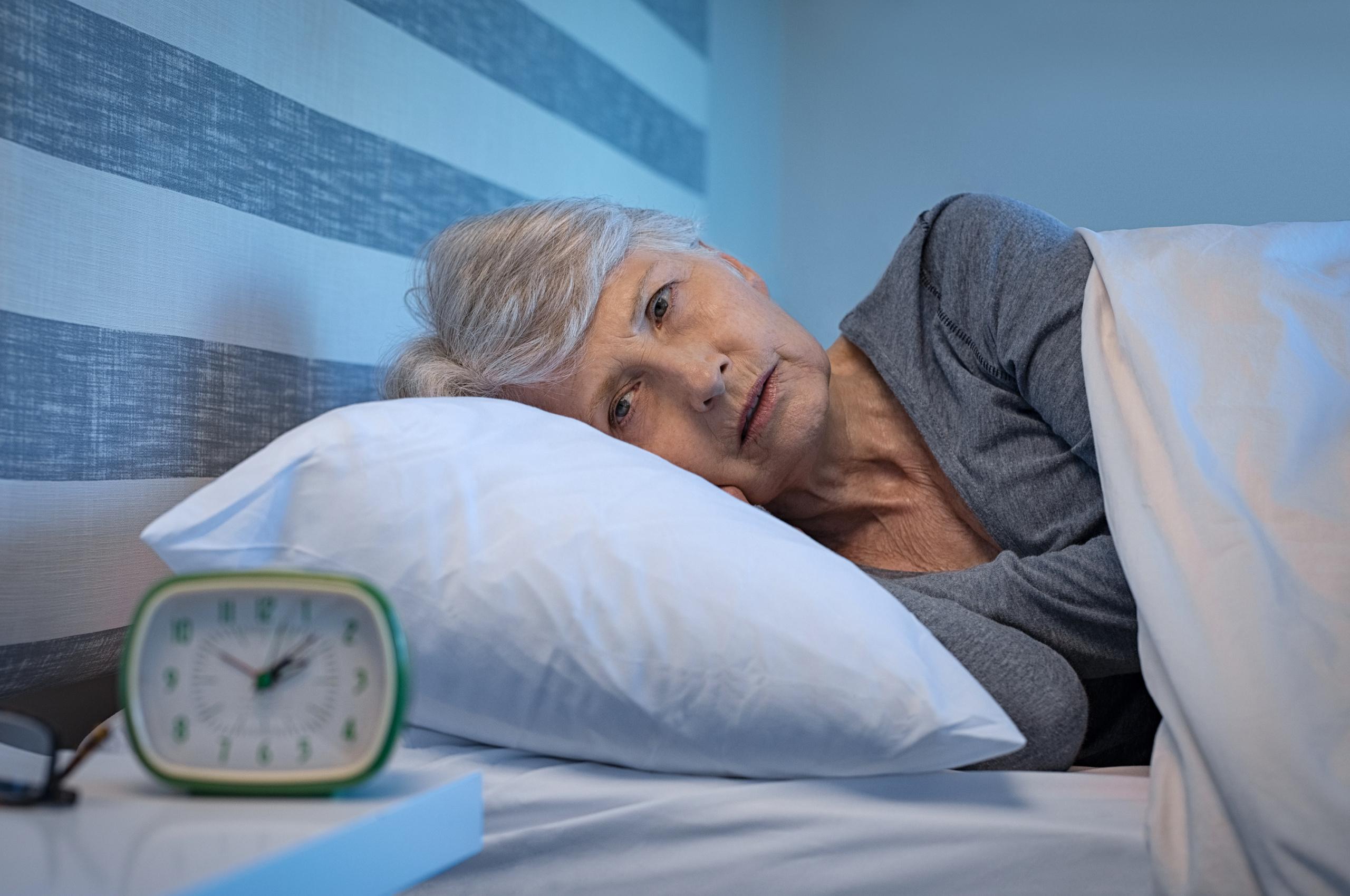Bildet viser en eldre kvinne som ligger og ikke får sove