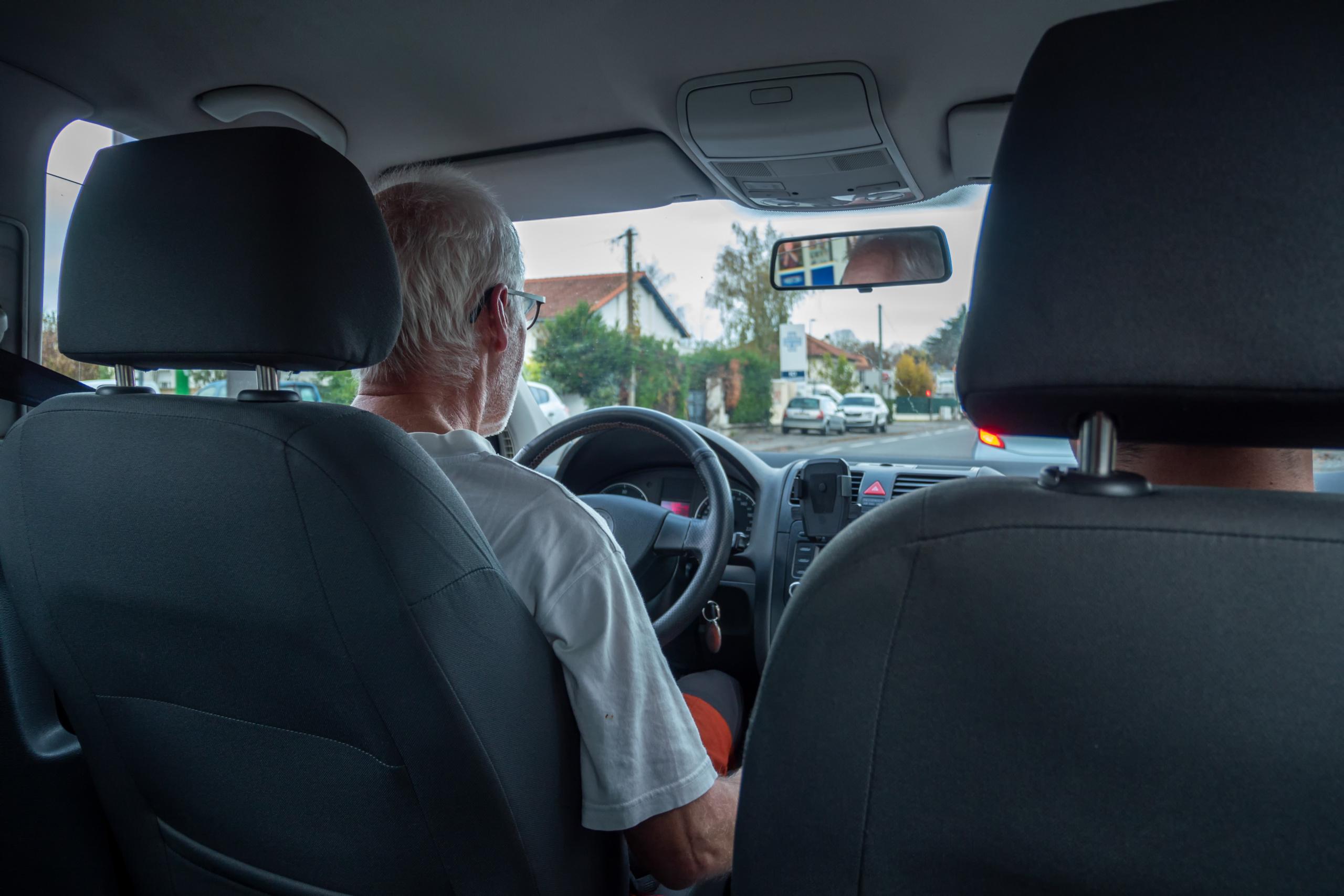 Eldre mann kjører bil. Foto.