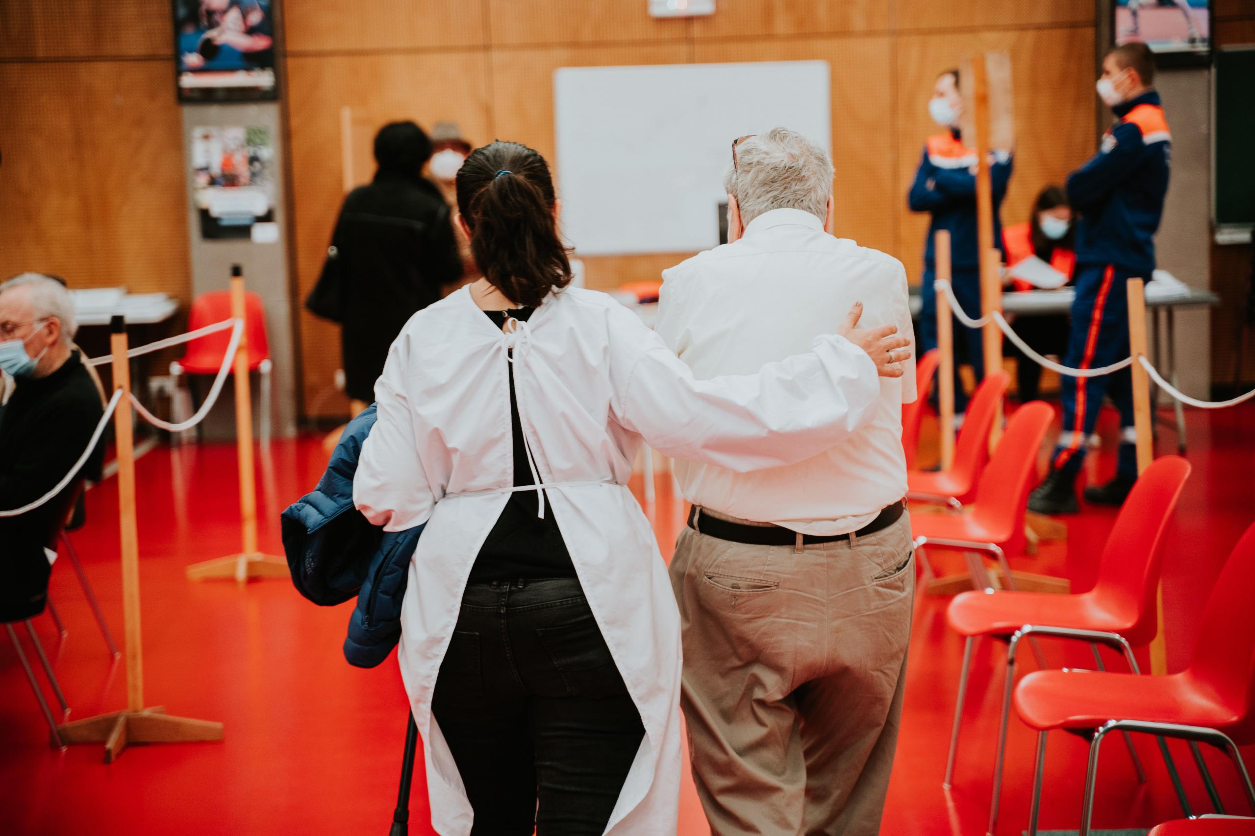 Kvinnelig helsepersonell holder arm rundt eldre mann, sett bakfra. Foto.