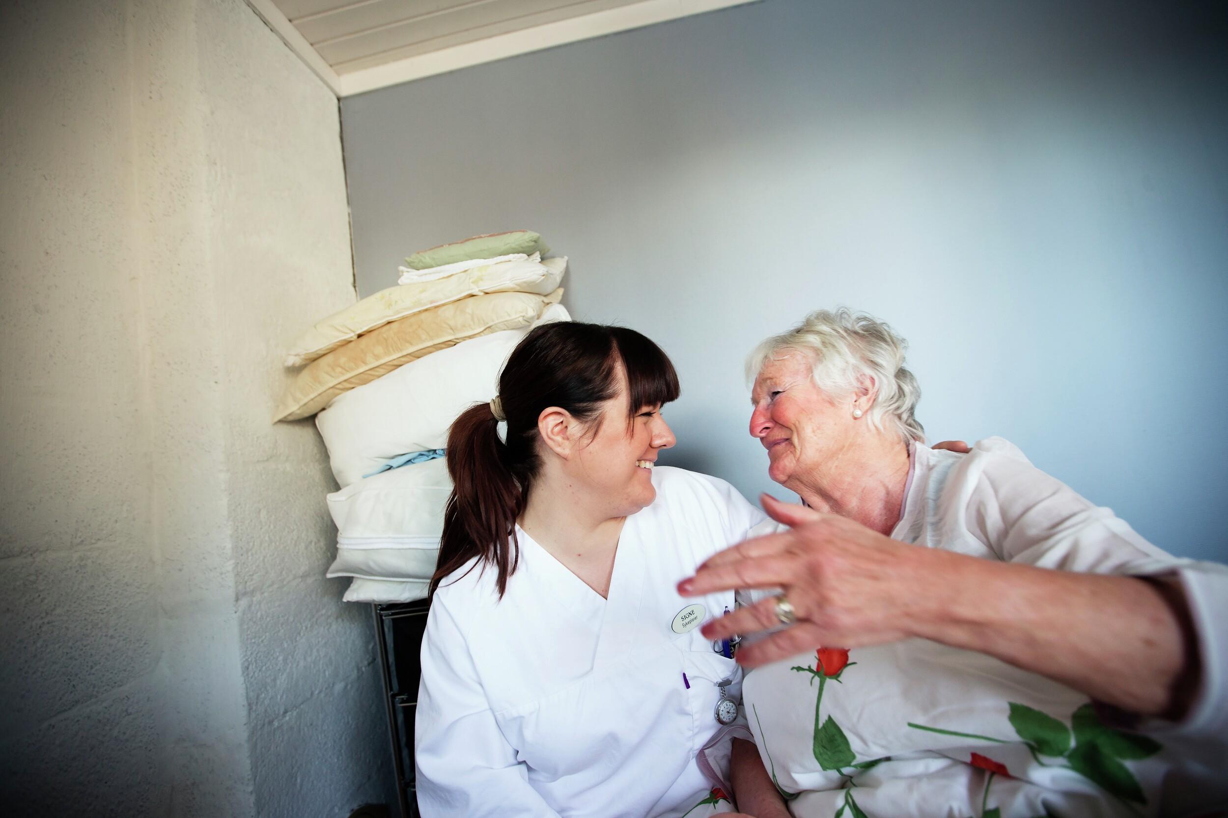 Pleier og eldre kvinne ler sammen. Foto.