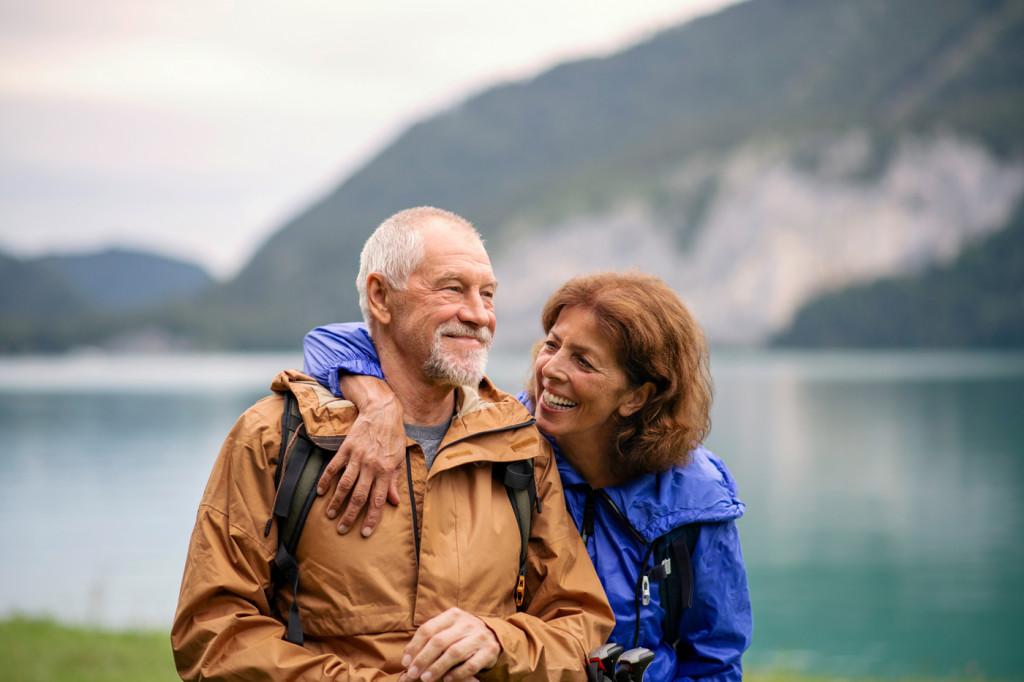 Smilende par foran innsjø med fjell bak. Foto.
