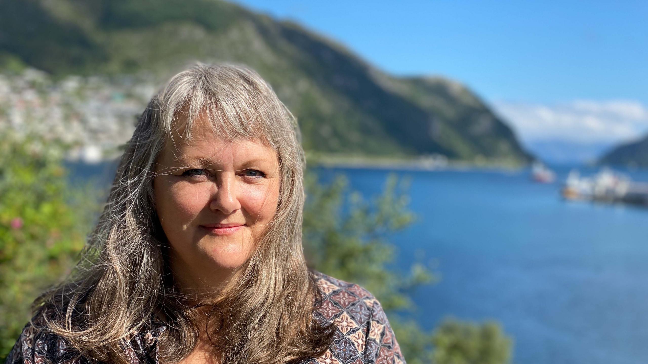 Portrett av kvinne med fjell og fjord i bakgrunnen. Foto.