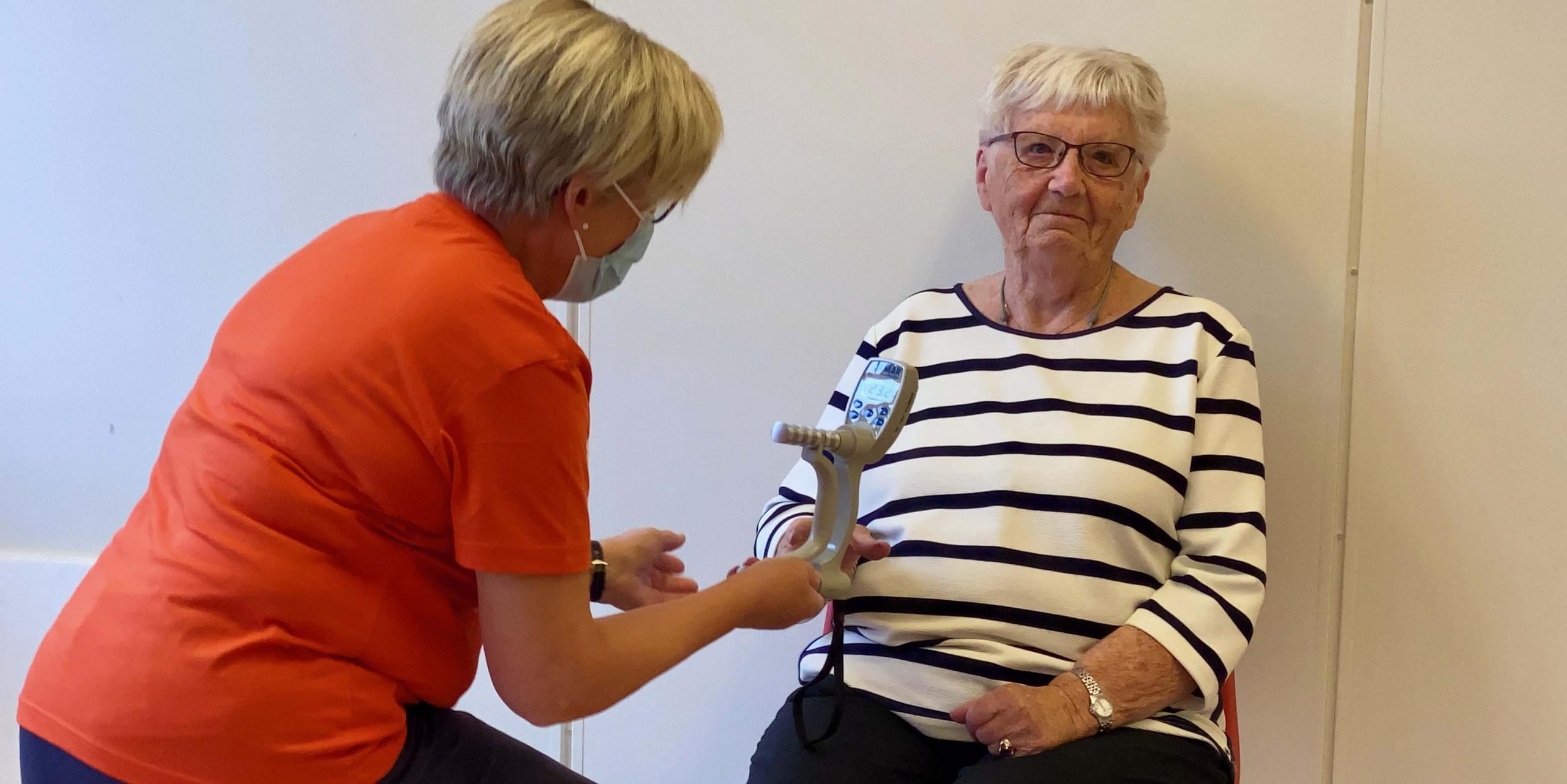 Eldre kvinne måler gripestyrke med helsepersonell tilstede. Foto.