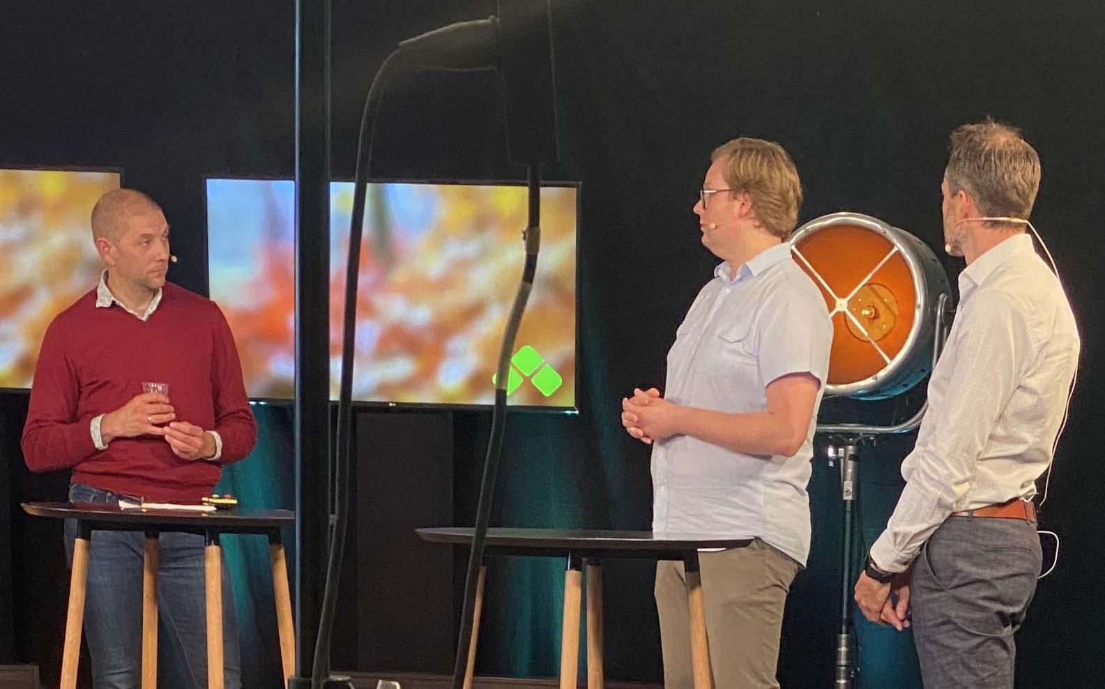 Tre menn diskuterer i studio. Foto.