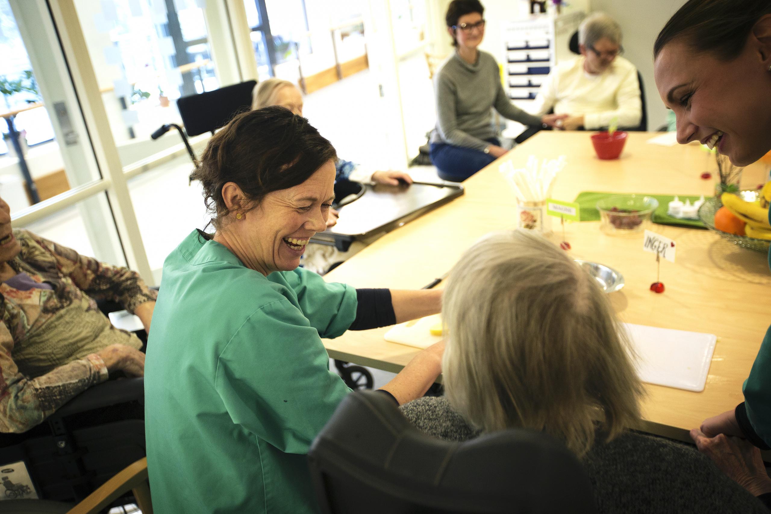 Helsearbeider smiler til eldre person