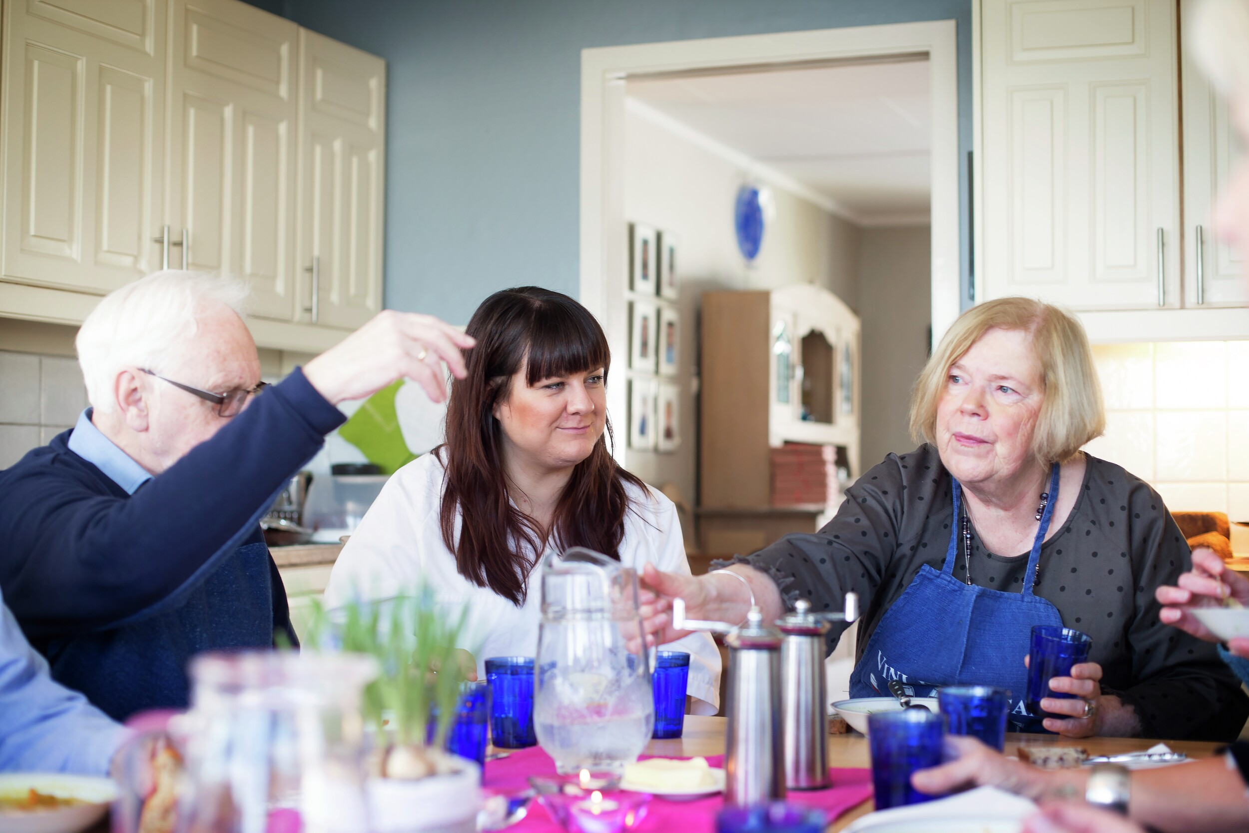 Personer rundt matbordet. Foto.