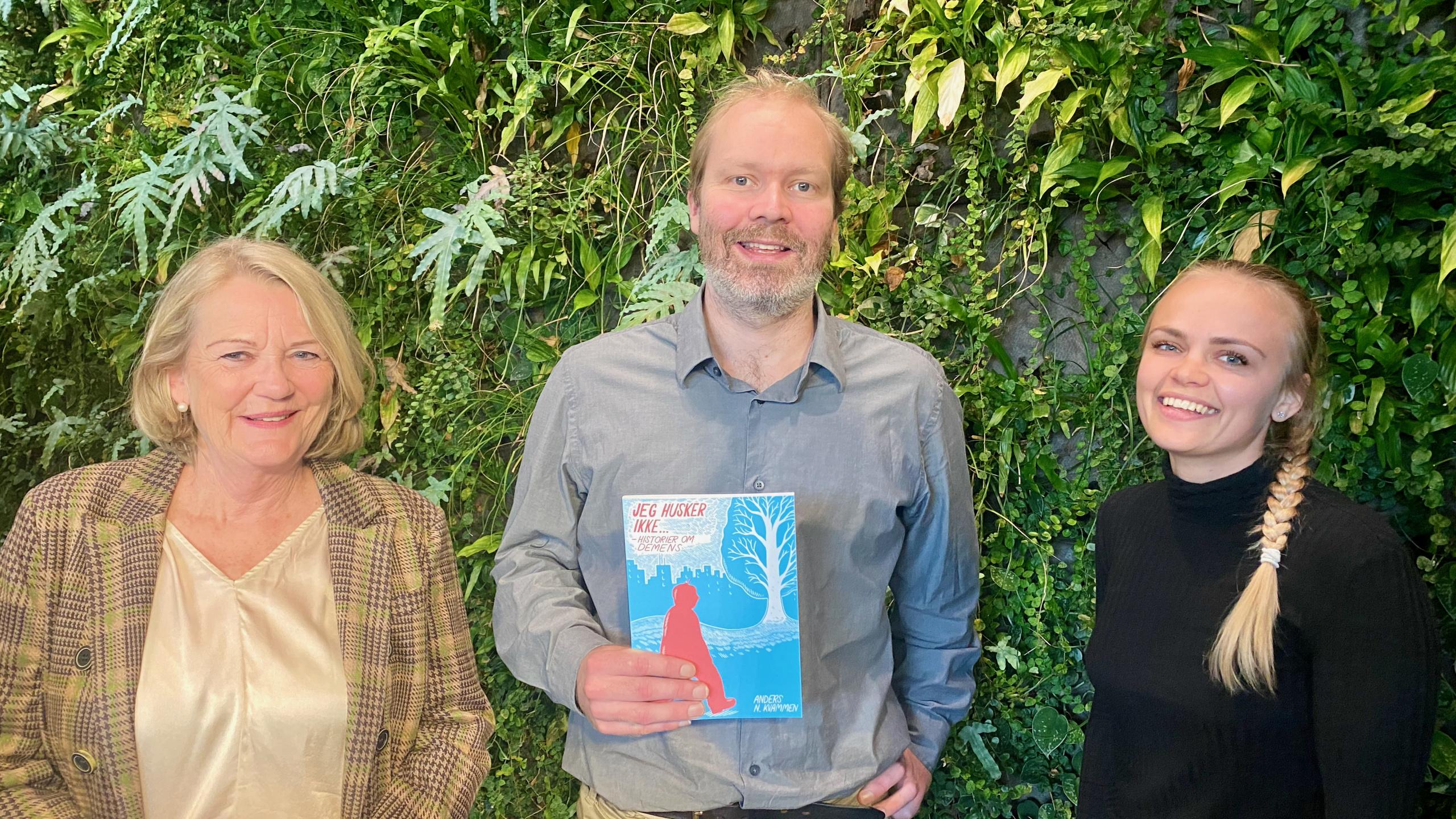 Mann med bok flankert av to kvinner.