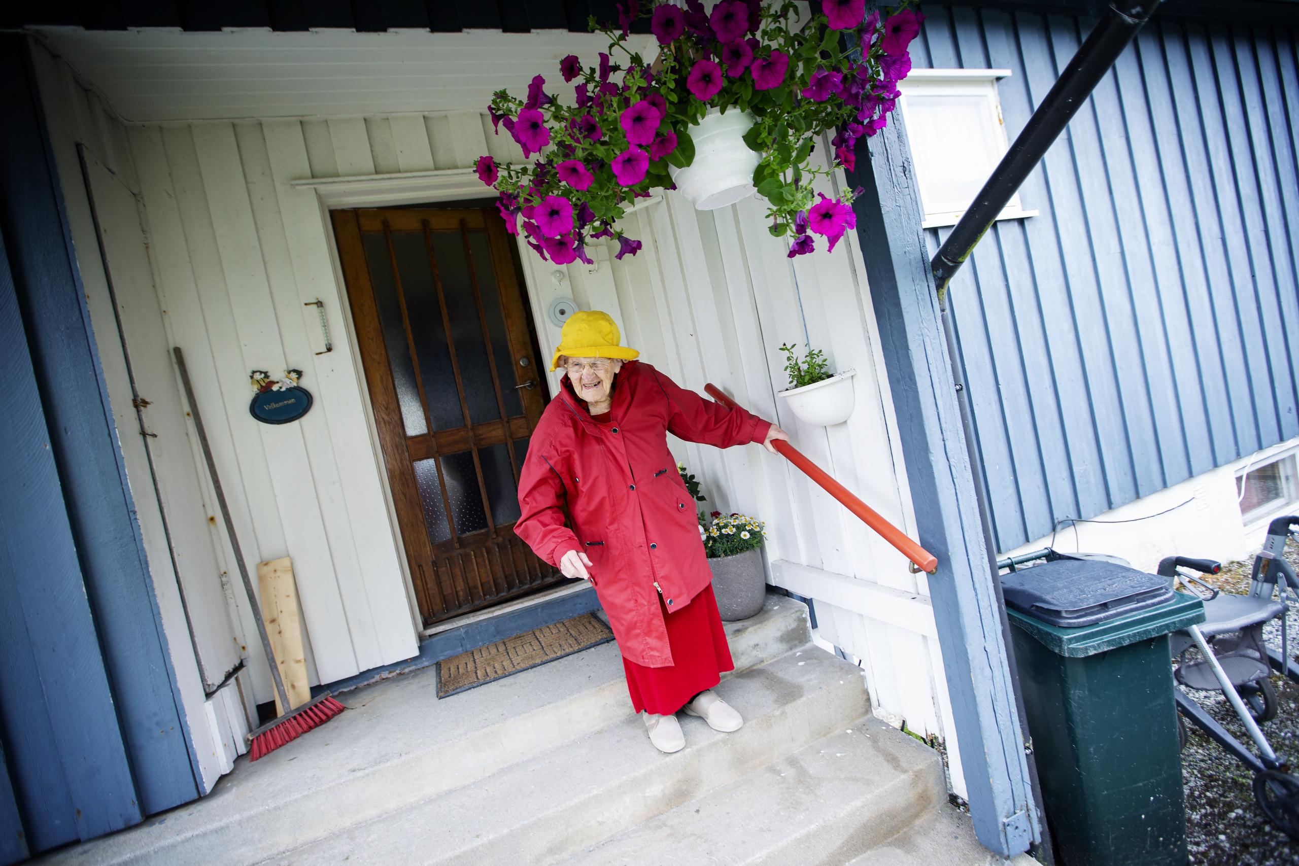 Eldre kvinne med sydvest og rød kappe kommer gående ned trapp